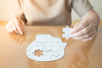 Elderly woman hands holding missing white jigsaw puzzle piece down into the place as a human head br...