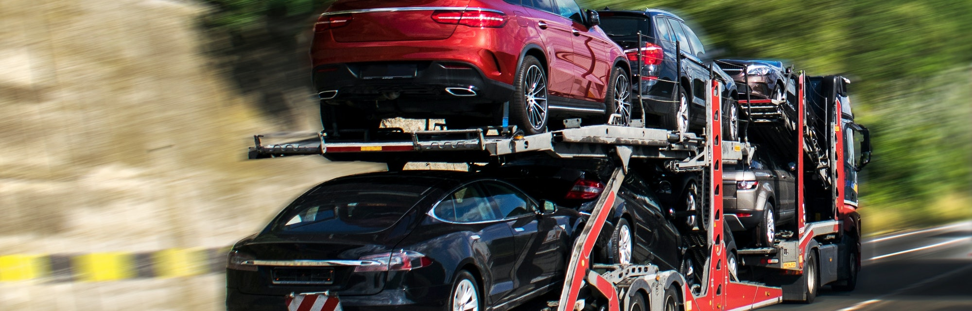 Hauling cars. A car carrier trailer, known variously as a car-carrying trailer, car hauler, auto transport trailer. Photo in motion. Panning. New and very expensive cars transportation.