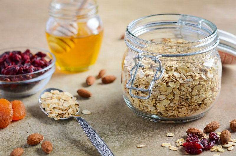 Ingredients for homemade oatmeal granola. Oat flakes, honey, almond nuts, dried cranberries and apricots. Healthy breakfast concept.