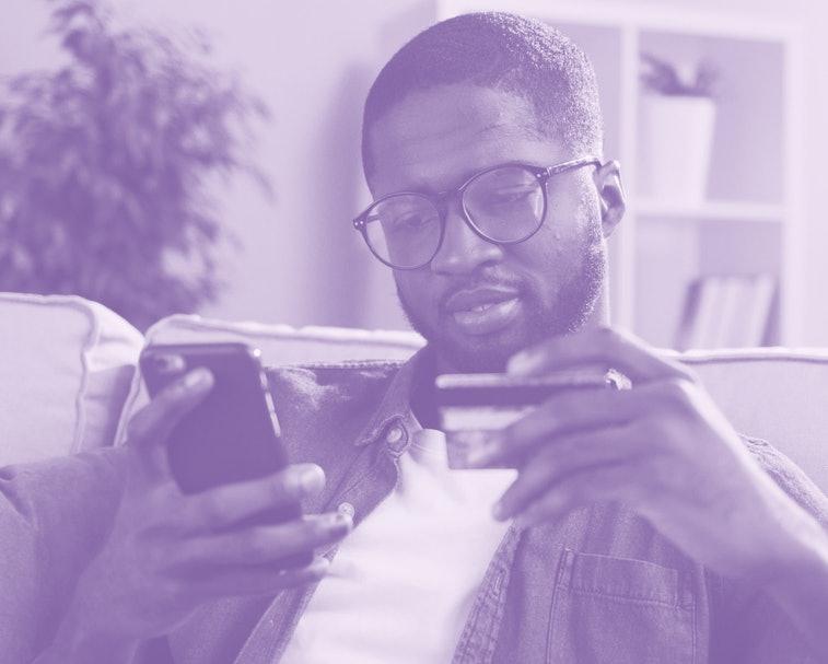 African young man in glasses shopping online with credit card using smart phone at home. Indoor.