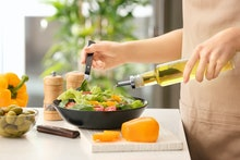 Woman dressing fresh vegetable salad with olive oil in kitchen
