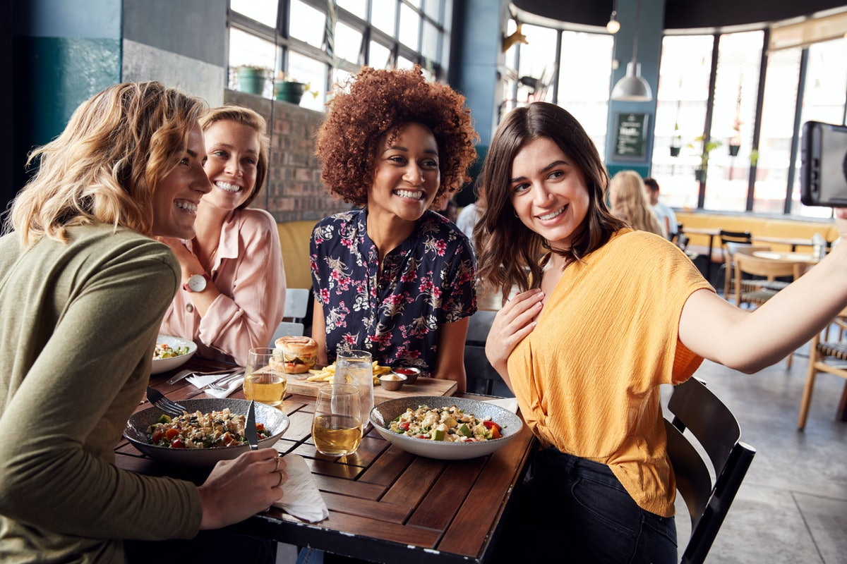 Four girls pose at a table at a restaurant for a selfie.