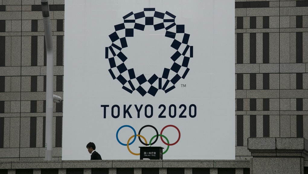 Man walks past a large banner promoting the Tokyo 2020 Olympics in Tokyo, . The IOC will take up to four weeks to consider postponing the Tokyo Olympics amid mounting criticism of its handling of the coronavirus crisis that now includes Canada saying it won't send a team to the games this year and the leader of track and field, the biggest sport at the games, also calling for a delay