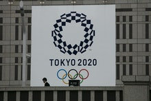 Man walks past a large banner promoting the Tokyo 2020 Olympics in Tokyo, . The IOC will take up to ...