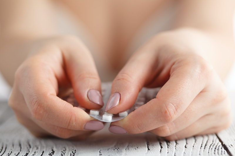 Contraceptive Pill in female hands ready to eat