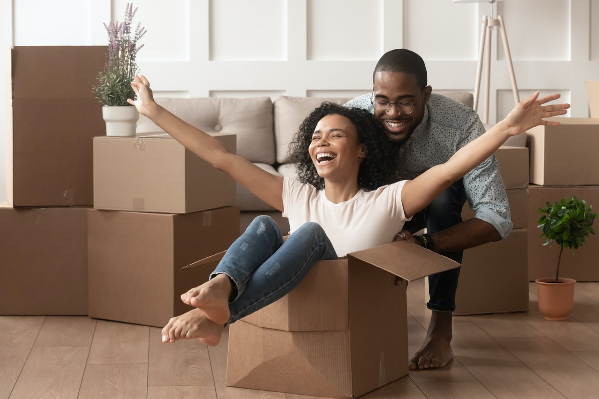 Two young Black people laugh in their new home, surrounded by cardboard boxes. Moving during COVID can be tough, but it's doable.