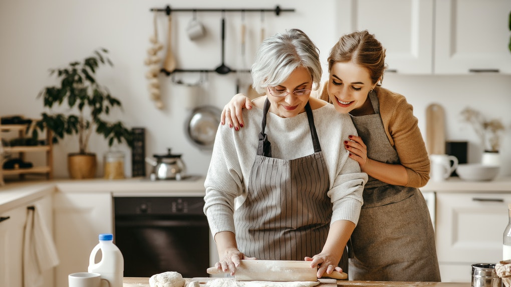 A happy mother and daughter bake together in the kitchen.