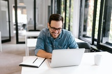 Cheerful businessman using laptop in bright office space.