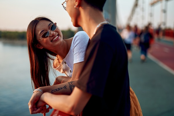 Love and date concept. Young happy stylish asian woman in cat eye sunglasses looking to her beloved man