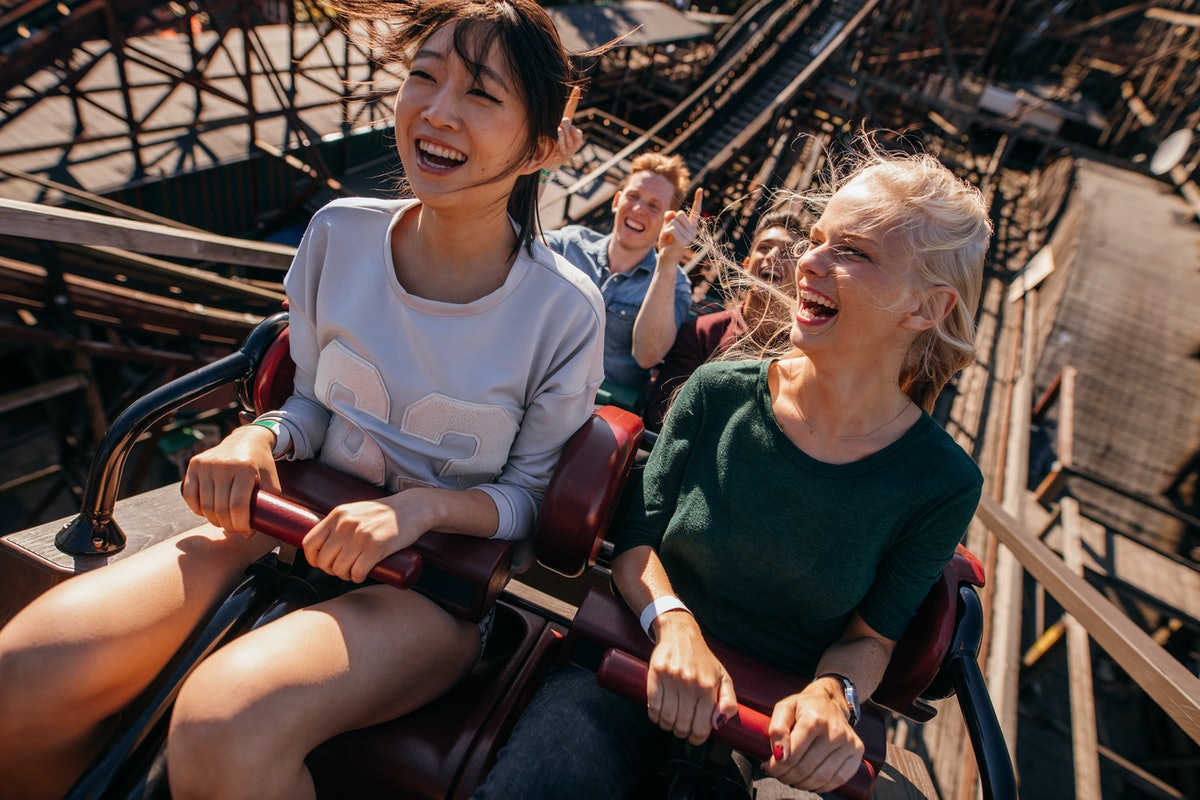 Two friends on a roller coaster laugh and smile right while going up a hill.