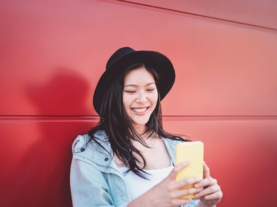 woman looking at her phone and laughing