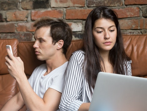 Young couple sitting back to back at home on couch addicted obsessed with modern gadgets, hipster guy using mobile phone while girlfriend overusing laptop avoiding ignoring each other after conflict
