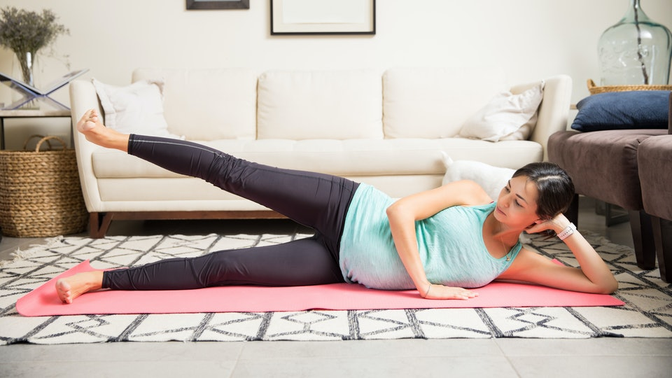 Full length of pregnant mother doing side leg lifts on fitness mat at home