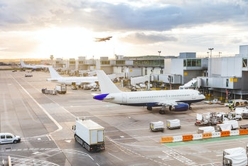 Busy airport view with airplanes and service vehicles at sunset. London airport with aircrafts at ga...