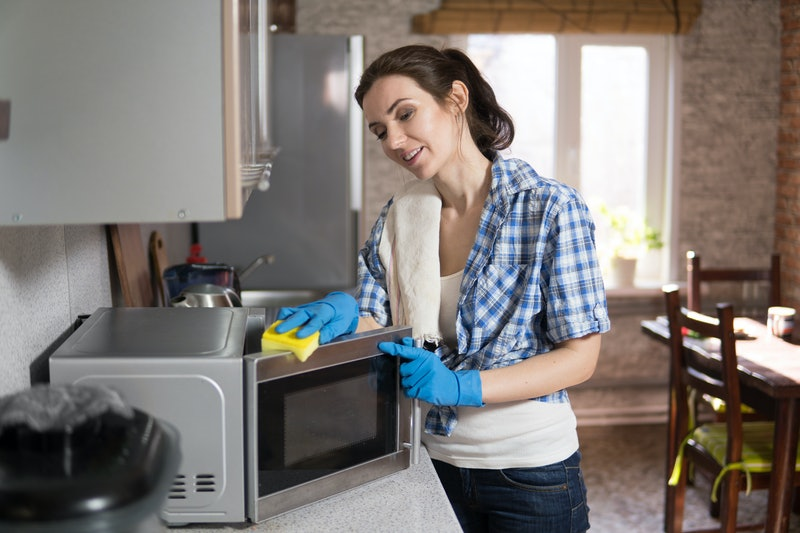 A young woman washes a microwave, a housewife taps into the kitchen