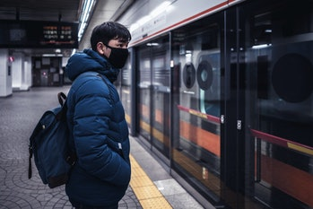 Asian male traveller cover mouth and cough, wear medical face mask to protect from infection of viruses, pandemic, outbreak and epidemic of disease in crowded underground train, Seoul South Korea