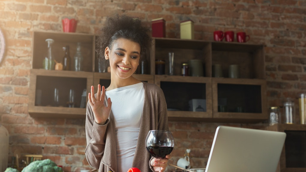 A happy woman standing in her kitchen at home waves at her computer and holds a glass of wine during a virtual call.