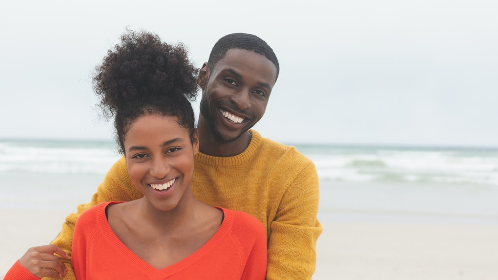 Portrait of diverse couple standing at beach on a sunny day. They are smiling and looking at camera