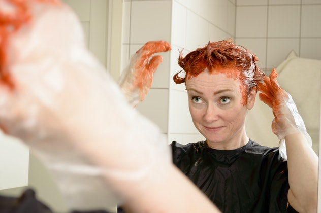 Caucasian woman with short hair dying her hair red in front of mirror in her own bathroom.
