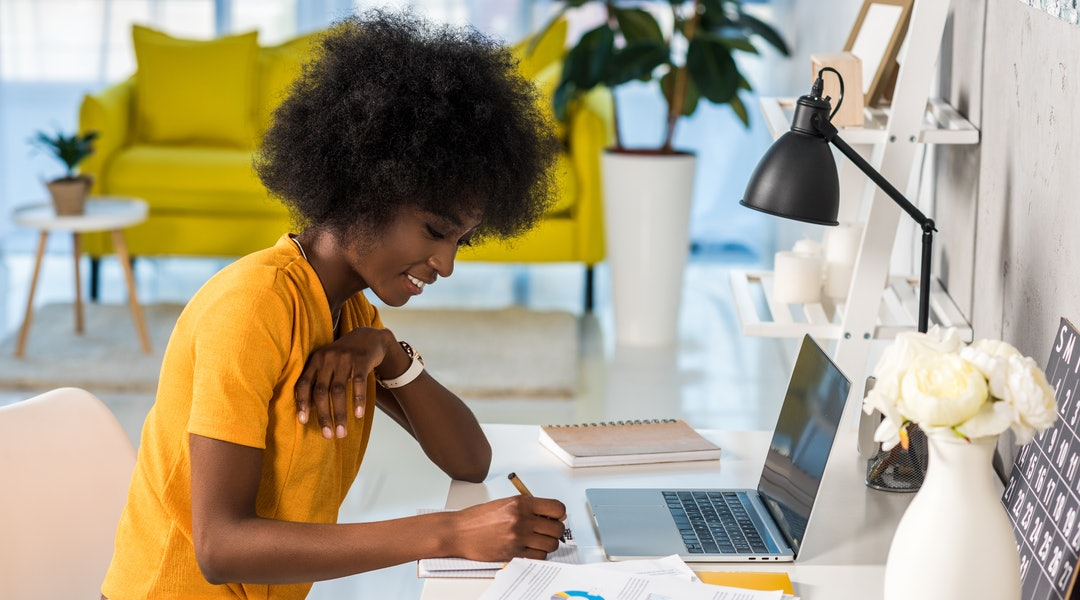 side view of smiling african american female freelancer working at home