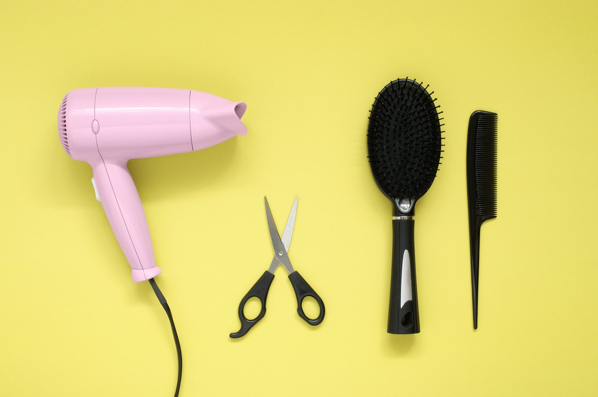 Pink hair dryer black brush, comb and scissors on yellow paper background