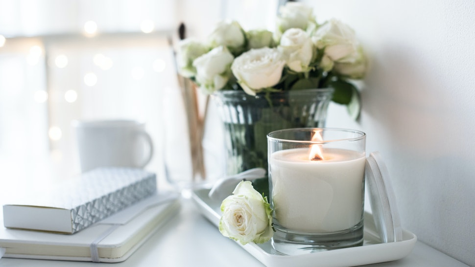 White room interior decor with burning hand-made candle and bouq