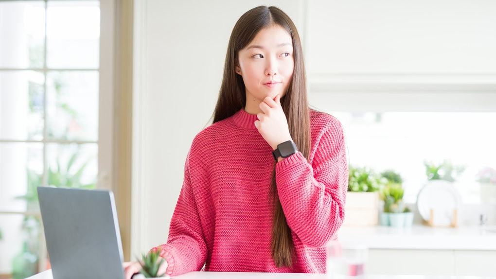 Beautiful Asian woman working using computer laptop serious face thinking about question, very confused idea