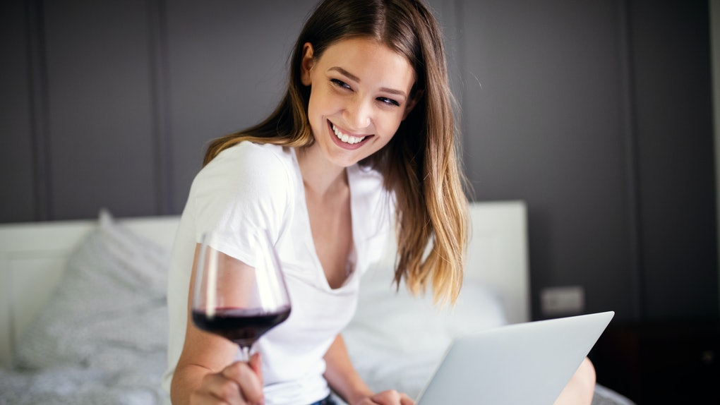 A brunette woman smiles and holds a glass of red wine and laptop on her lap.
