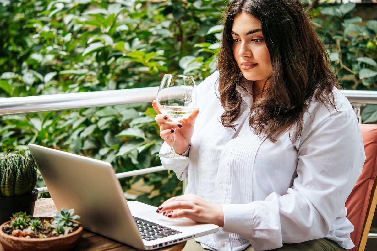 A woman sitting on her balcony outside, enjoys a glass of wine during a virtual wine tasting on her ...