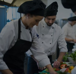 Professional team cooks and chefs preparing meals at busy hotel or restaurant  kitchen