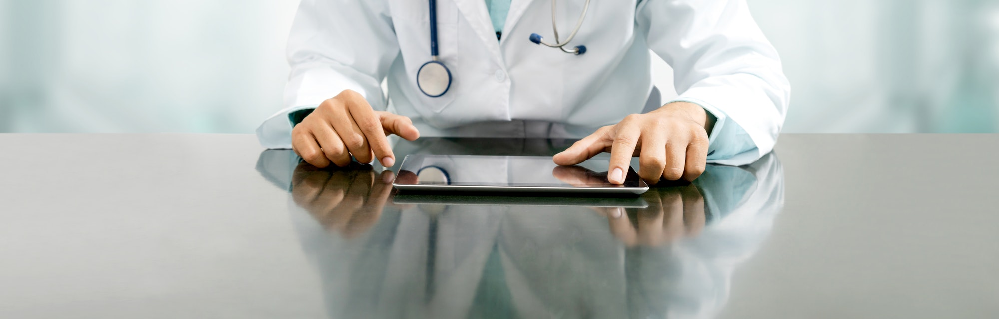 Male doctor sitting at table with tablet computer in hospital office. Medical healthcare staff and doctor service.
