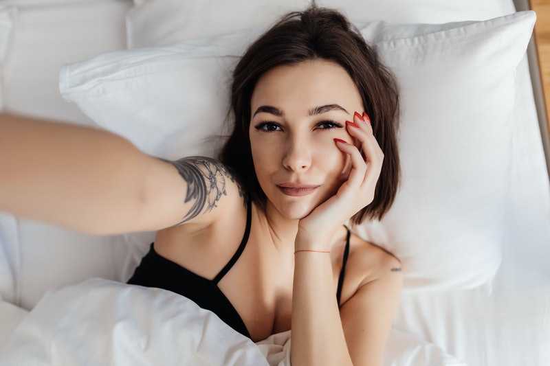 Beautiful girl making selfie in the bed. Beautiful girl making self on the bed at home. Selfie in the morning