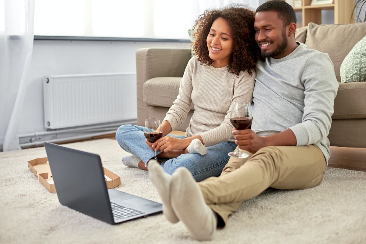 A couple relaxes at home, drinking wine, while watching a virtual wine tasting on their computer.