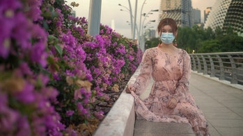Asian Chinese girl wearing a surgical face mask to protect herself from COVID-19 coronavirus infection in crowded public places in downtown Singapore at sunset