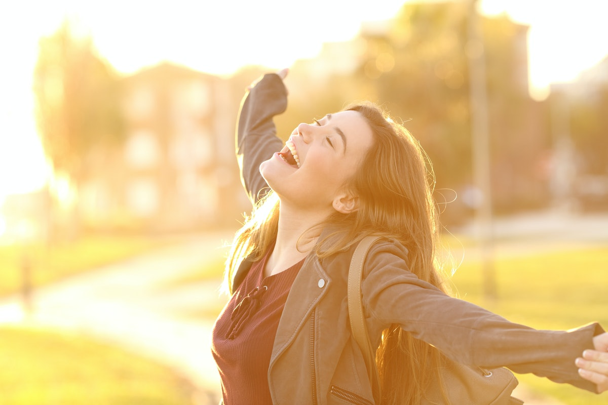 Portrait of an excited teenager girl raising arms and laughing in the street at sunset with a warm light in the background
