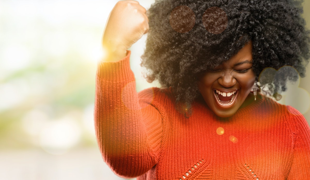 Beautiful african woman happy and excited expressing winning gesture. Successful and celebrating victory, triumphant, outdoor