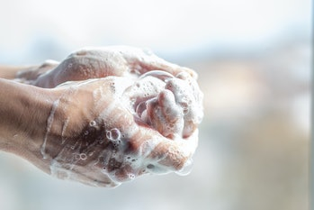 A man washes his hands with soap. Man's hands in foam with bubbles