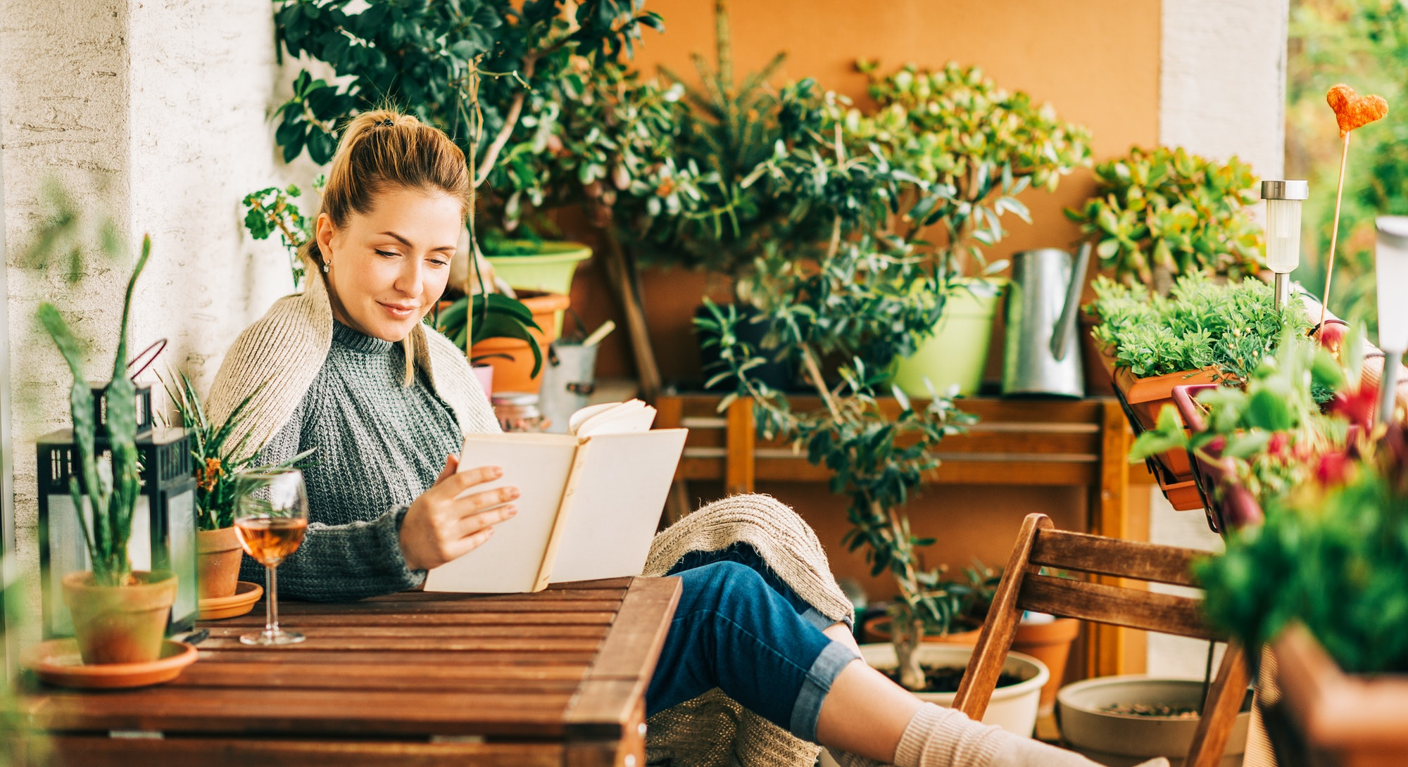 A blonde woman on a patio sits surrounded by plants, reading a book.