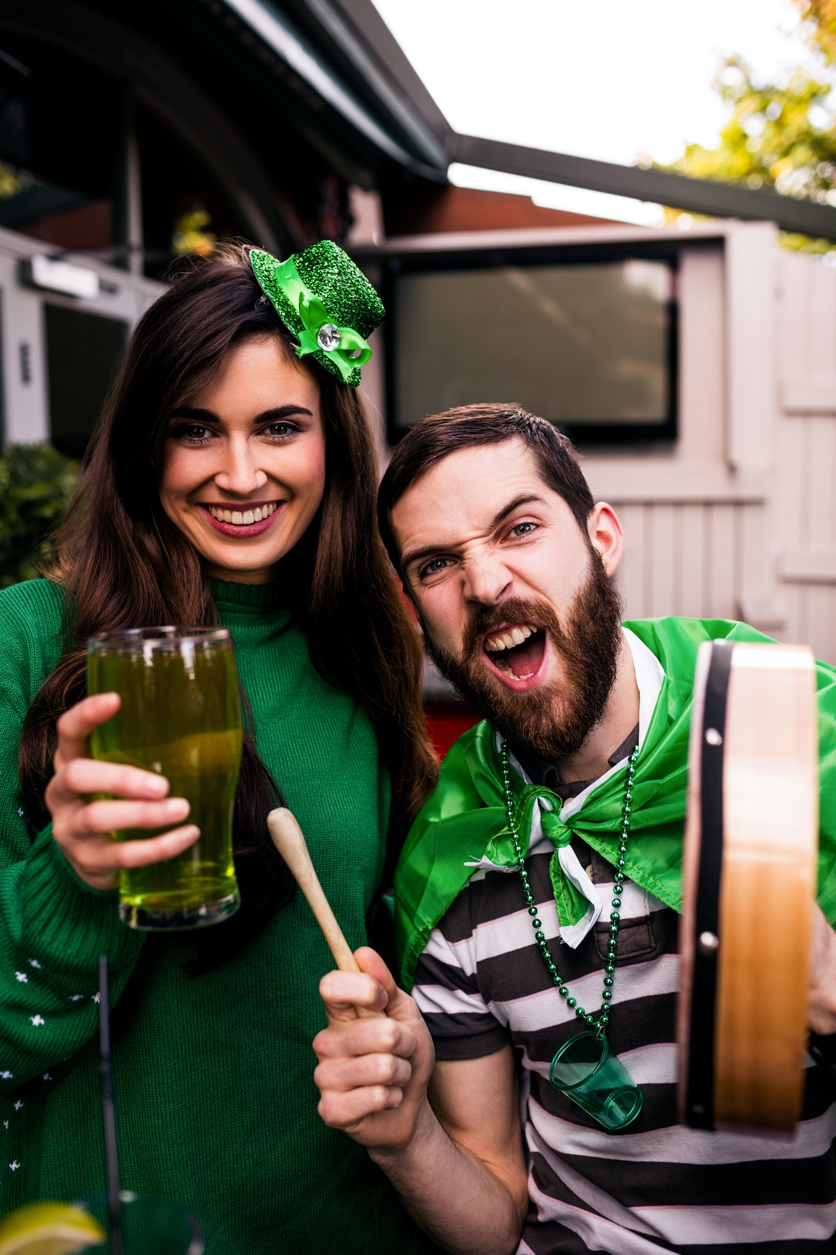 A young couple hangs out in a bar on St. Patrick's Day and drinks green beer.