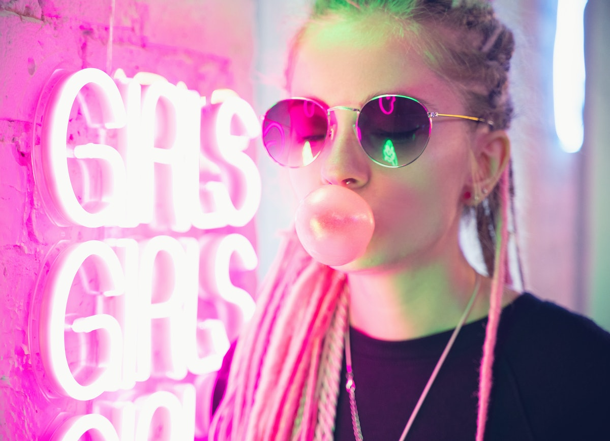A woman with long pink hair who's wearing sunglasses and blowing a bubblegum bubble stands in front of a neon pink sign in the city.