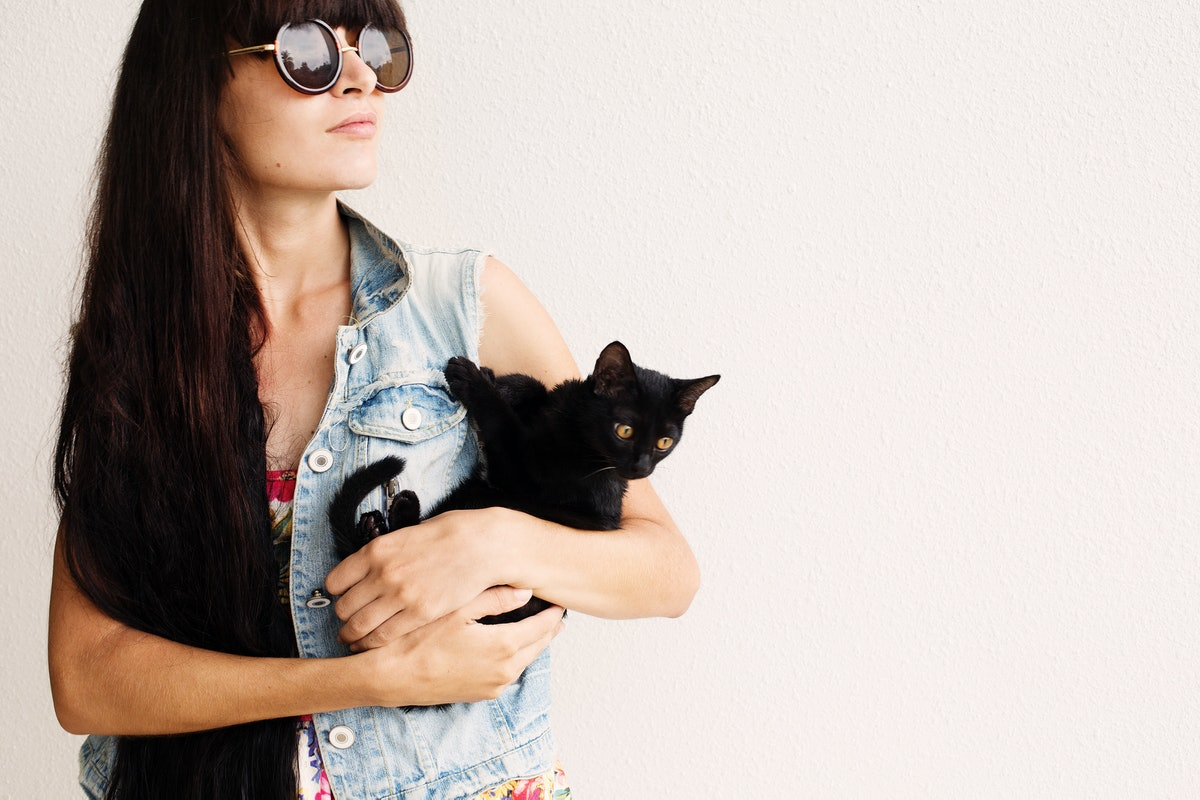 A woman with long brown hair wearing sunglasses and a denim vest holds her black cat.