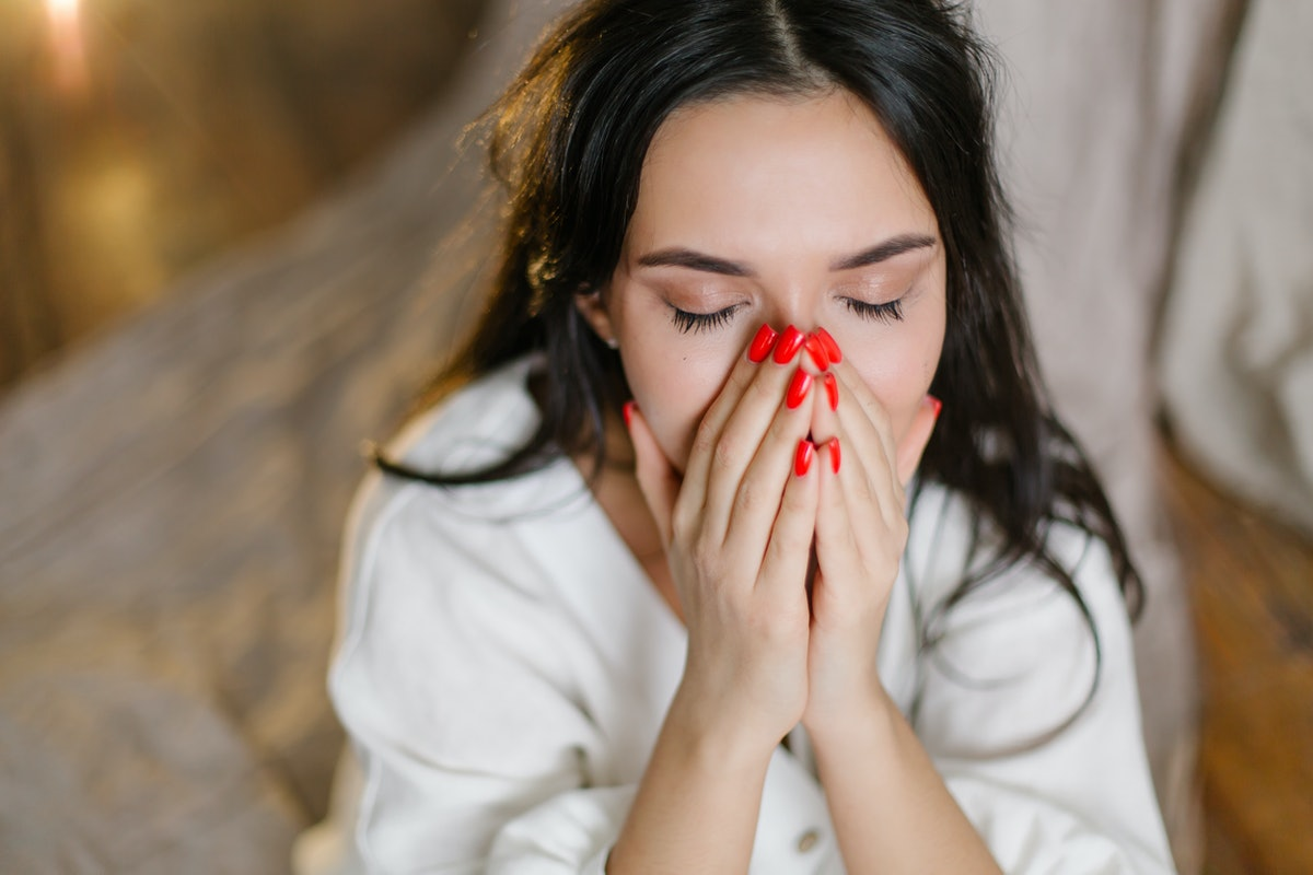 A beautiful oriental girl crying closes her eyes with her hand in a depressed state. Diagnosis psych...