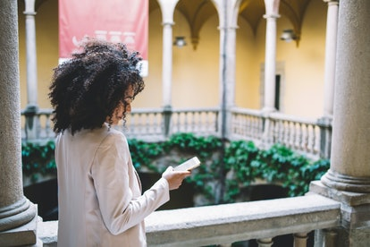 Back view of ethnic female in casual outfit standing on terrace and using smartphone outside aged building in Barcelona, Spain