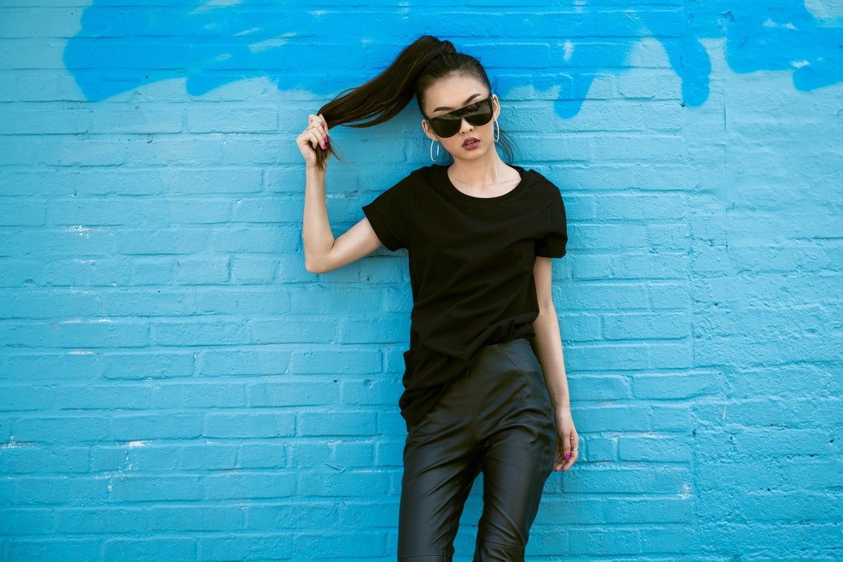 A fashionable woman wearing a black tee, leather leggings, and sunglasses poses against a blue brick wall.