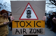 A Romanian environment activist young woman waves a placard during a protest, named 'Clean air, not ...