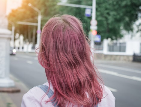 Hipster woman pink head back view, city street