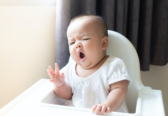 Asian baby girl sitting and yawning on  white high chair