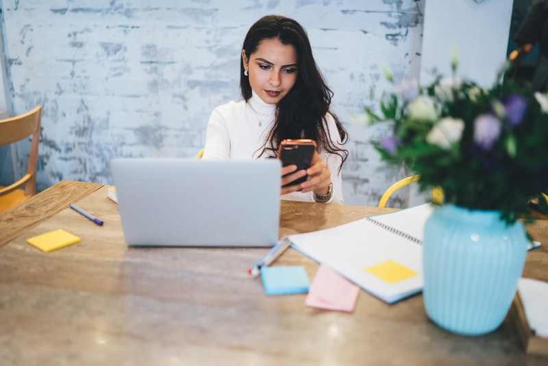 Young attractive woman in casual wear using phone discussing with colleague strategy of project spending time sitting at table in cafe