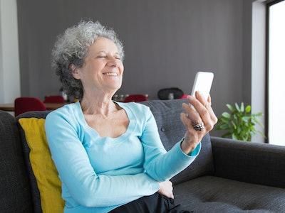 Grandmother looking at phone, laughing at april fools' day prank