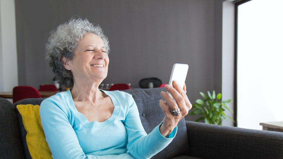Grandmother looking at phone, laughing at april fools' day prank